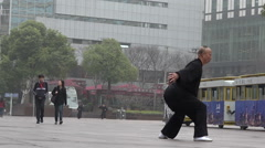 Chinese man practice Tai Chi in Nanjing Road Shanghai China Stock Footage