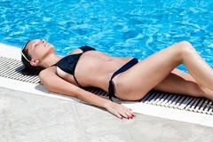 Sexy woman lying near the pool Stock Photos