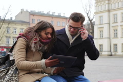 Couple sitting on the bench on public square and using modern technology Stock Footage