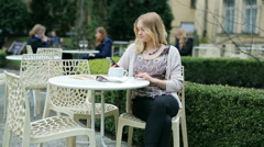 Impatient girl waiting for someone in the outdoor cafe - stock footage