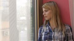 Sad and lonely young woman looks out of the window: depressed woman Stock Footage
