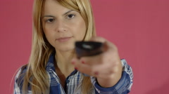 Young woman using tv remote control to change tv programs Stock Footage