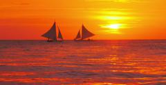 Sunset sky and sailing boats on tropical sea coast. Big yellow sun on horizon - stock footage
