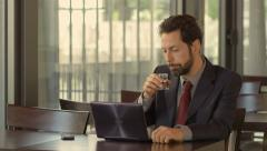 Businessman drinks alcohol while works with his laptop sitting in a cafè Stock Footage