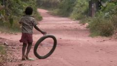 Africa: young boy playing with tire on dirt road Stock Footage