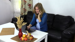 Pregnant business woman talk phone and work with laptop at home Stock Footage