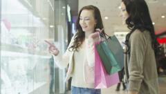 Two Girls are Looking at Display Window of Jewelry Store in Shopping Mall Stock Footage
