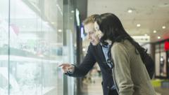 Young Couple is Looking at Display Window of Jewelry Store in Shopping Mall. - stock footage