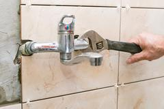 Water fixing - plumber hands with wratch fix tap Stock Photos
