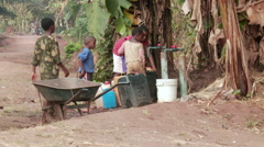 Africa: children filling jerrycans with water in jungle Stock Footage