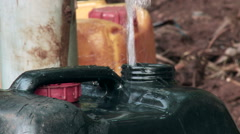 Jerrycan being filled with water in jungle, close shot Stock Footage