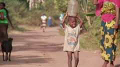 Africa: small boy with plastic bottle on head in bush. Stock Footage