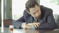 Depressed businessman sitting in a cafè with a glass of alcohol Stock Footage