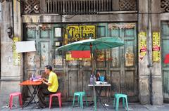 Unidentified man eats on a street in Chinatown district, Bangkok, Thailand Stock Photos