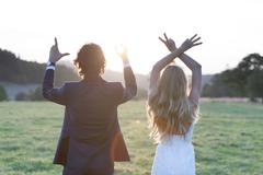 """Married couple standing at the sunset, forming by fingers the word """"LOVE"""". Stock Photos"""