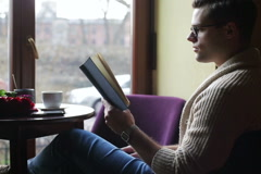 Man reading book and answer phone in the restaurant Stock Footage
