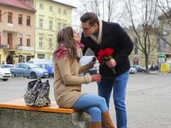Woman waiting on public square and man giving her bunch of red roses Stock Footage