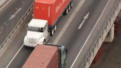 Stock Video Footage of View from above to the trucks loaded with cargo containers passing by the road.