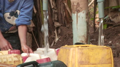 Africa: jerrycans filling with water in bush Stock Footage