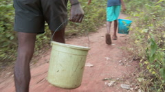 Africa: men carrying water on jungle path Stock Footage
