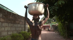 Africa: man carrying heavy pan with water on head Stock Footage