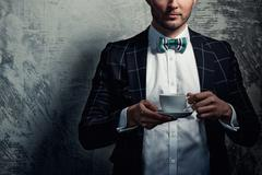 Sharp dressed fashionist with cup of coffee - stock photo