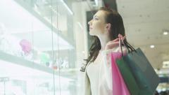 Young Pretty Girl with Shopping Bags is Looking at Display Window Stock Footage