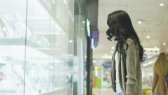Young Pretty Girl is Looking at Display Window of Jewelry Store in Shopping Mall Stock Footage