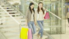 Two Girls with Shopping Bags are Moving Down The Stairs in Shopping Mall Stock Footage