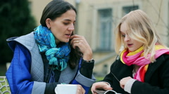 Girl answer the phone while talking with her friend in the cafe Stock Footage