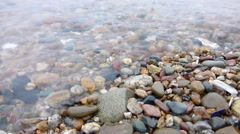 Close-up view of the pebbles and waves at the beach - stock footage