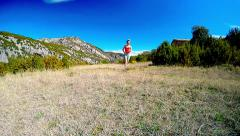 Young woman running on mountain trail in alpine pasture with mountain summits Stock Footage