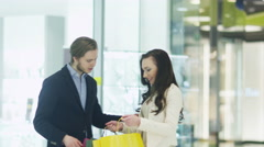Girl is Showing her Purchases to Boyfriend in Shopping Mall - stock footage