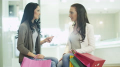 Two Girls are Sitting and Talking in Shopping Mall - stock footage