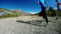 young couple running away on mountain trail in the alpine meadow - stock footage