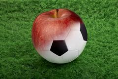 Soccer ball on green grass to apple Stock Illustration