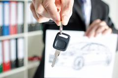 Salesman holding a key and showing a car design - stock photo