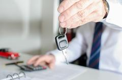 Car salesman holding a key - stock photo