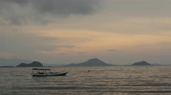 Labuan Bajo beach sunset with fishing boat Stock Footage