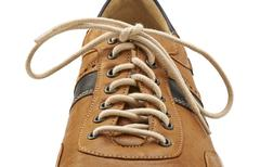 Shoelace in close up and brown shoe isolated on white Stock Photos