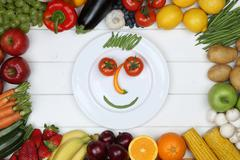 Healthy vegetarian eating smiling face from vegetables and fruits on plate - stock photo