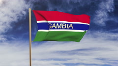 Gambia flag with title waving in the wind. Looping sun rises style.  Animation Stock Footage