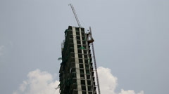 Unfinished and halted building project, crane on top, day, with blue sky  Stock Footage
