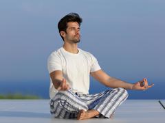 Young man practicing yoga Stock Photos