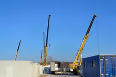 cranes and unloads trucks at constructionsite - stock photo