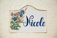 Nicole - old tile on city street wall with flower and beautiful handwriting Stock Photos