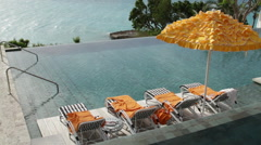 Infinity pool on the deck of a fancy resort with beach chairs Stock Footage