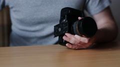 Guy tripod base unscrews from the camera Stock Footage