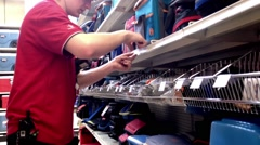 Worker exhibiting goods and checking price in Canadian tire store Stock Footage