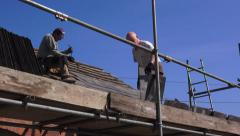 Builders removing roof slates from old barn Stock Footage